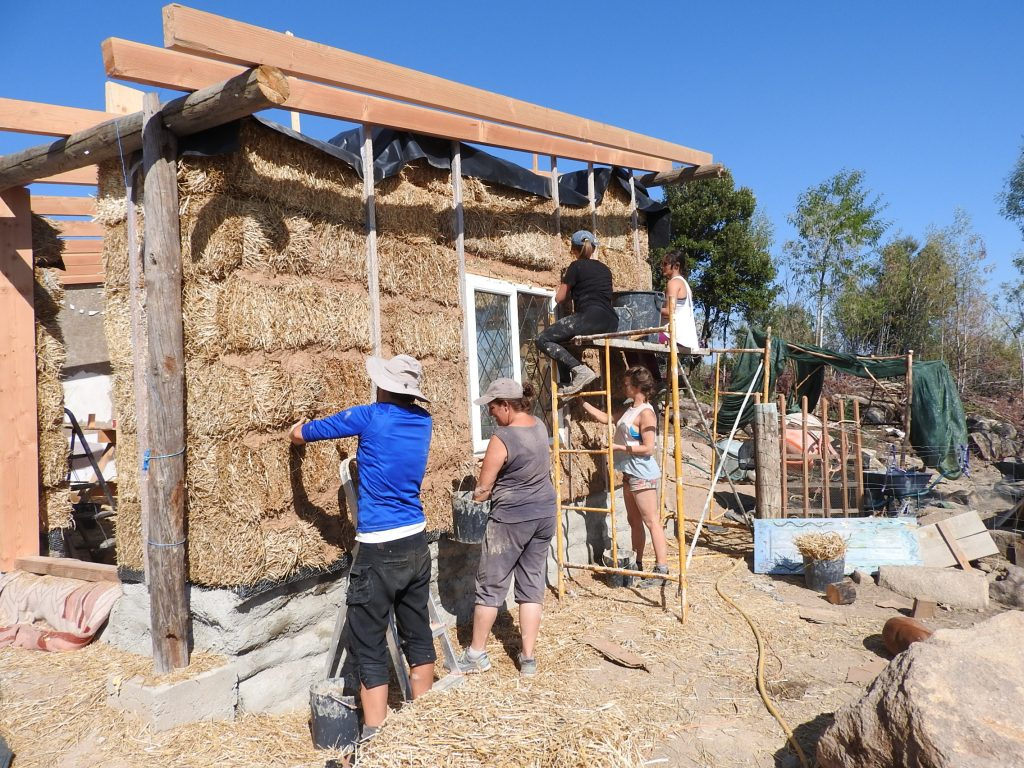Plastering the strawbale house with clay